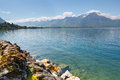 Landscape shore of the lake and snow capped mountains on a sunny day panorama Royalty Free Stock Photos