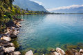 Landscape shore of the lake and snow capped mountains on a sunny day panorama Stock Images