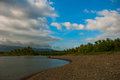 Landscape sky with clouds, volcanic sand on the beach. Pandan, Panay, Philippines. Royalty Free Stock Photo