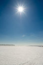 Landscape of a snow-covered field and blue sky. Stock Image