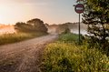 Landscape sunny dawn with road and road sign fog Royalty Free Stock Image