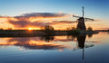 Landscape with traditional dutch windmills at colorful sunrise Royalty Free Stock Photo