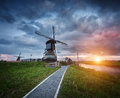Landscape with traditional dutch windmills and path near the water canals. Royalty Free Stock Photo