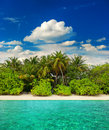 Landscape of tropical island beach with palm trees and cloudy blue sky view from water travel destination Royalty Free Stock Photography