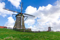 Landscape two aligned windmills alignment of a long of a calm canal and the farmer land at the hague netherlands Stock Photos
