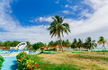 Landscape view of hotel grounds with swimming pool and people relaxing and enjoying their time on sunny day Royalty Free Stock Photo