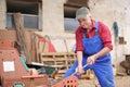 Landwirt der seinen roten traktor repariert Lizenzfreie Stockfotos
