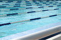 Lanes of swimming pool over light blue transparent  water. Royalty Free Stock Photo