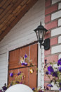 Lantern over a door under cattle roof about and dark blue flowers Stock Image