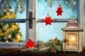 Lantern on window sill in winter mood christmas tree background Stock Photos