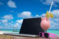 Laptop blank screen on wooden desk with beach. relax concept. Royalty Free Stock Photo
