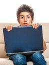 Laptop boy shocked behind big sitting on sofa expression isolated on white background Stock Photos