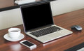 Laptop, cell phone, coffee cup on wood table background in office