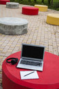 Laptop on the cement table red in park Royalty Free Stock Photos