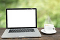 Laptop computer with coffee cup on wooden  with defocus of garde Royalty Free Stock Photo