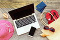 Laptop computer and smart phone with beach accessories on wooden board Royalty Free Stock Photo