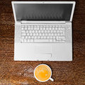 Laptop and cup of coffee on table view from above Stock Photography