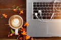 Laptop, earphone and flower with a cup of coffee on old wooden table Royalty Free Stock Photo