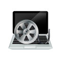 Laptop and film reel isolated on white background Stock Photography