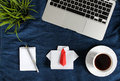 Laptop keyboard, white origami shirt with red tie near white cup of tea on saucer dark blue crumpled jeans background. Royalty Free Stock Photo