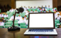 Laptop and microphone on the rostrum in empty conference hall Stock Image