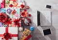 Laptop and plenty of gifts tablet smart phone on a desk with colorful celebrations christmas concept top view Stock Image