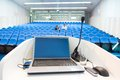 Laptop on the rostrum in conference hall and microphone with blue velvet chairs Royalty Free Stock Images