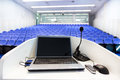 Laptop on the rostrum in conference hall and microphone empty with blue velvet chairs Stock Photo