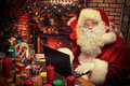 Laptop santa claus sitting at the table with a at his home christmas time Royalty Free Stock Image