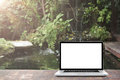 Laptop on wooden floor with fish pond and garden background. Royalty Free Stock Photo