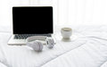The laptop working on the white bed and coffee in the sunny day morning holiday. Royalty Free Stock Photo