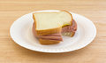 Large bitten bologna sandwich on paper plate Royalty Free Stock Photo