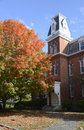 Large brick building in stonington connecticut red there is a tree by the structure with colorful autumn leaves Stock Photography