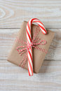 Large candy cane small present high angle shot of a on a plain brown paper wrapped christmas vertical format on a rustic white Stock Images