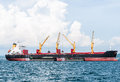 Large cargo ship modern carn in the is lifting the goods from small Royalty Free Stock Photo