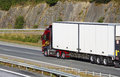 Large clean truck on the move driving along mountain pass sideways view freeway Royalty Free Stock Images