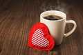 Large cup of hot drink and heart textile on a wooden table. The concept of Valentine's day holiday Royalty Free Stock Photo