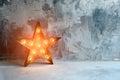 Large decorative retro star with lots of burning lights on grunge concrete background. Beautiful decor, modern design Royalty Free Stock Photo
