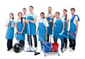 Large diverse group of janitors with equipment wearing blue aprons standing grouped together their smiling at the camera isolated Stock Images