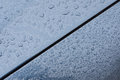 Large drops of rain on the hood of a car, paint texture of a blue metallic paint Royalty Free Stock Photo