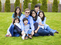 Large family of seven sitting together on lawn Stock Photo