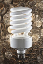 Large fluorescent bulb on gold dollar coins. Stock Photography