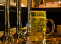 Large glass tankard of draught beer close up view standing on bar counter at foot stainless steel taps for dispensing Royalty Free Stock Images