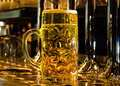 Large glass tankard of draught beer close up view a standing on bar counter at foot stainless steel taps for dispensing Royalty Free Stock Images