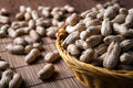 Large grains of peanuts in the shell and basket Royalty Free Stock Photo