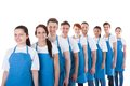 Large group of cleaners standing in a line diverse or janitors queue receding diagonal to the camera wearing blue aprons Royalty Free Stock Photos