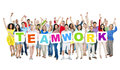 Large group of diverse people holding teamwork multi ethnic casual white placards with letters forming the word Stock Images