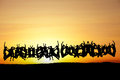 Large group of teens jumping in sunset silhouetted Royalty Free Stock Photos