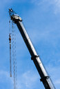 Large heavy industrial crane extended with pulleys and hanging c fully into sky cables down from top weight hooks on chains Stock Images