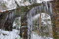 Large icicles hanging from a stone aquaduct archway Royalty Free Stock Photography